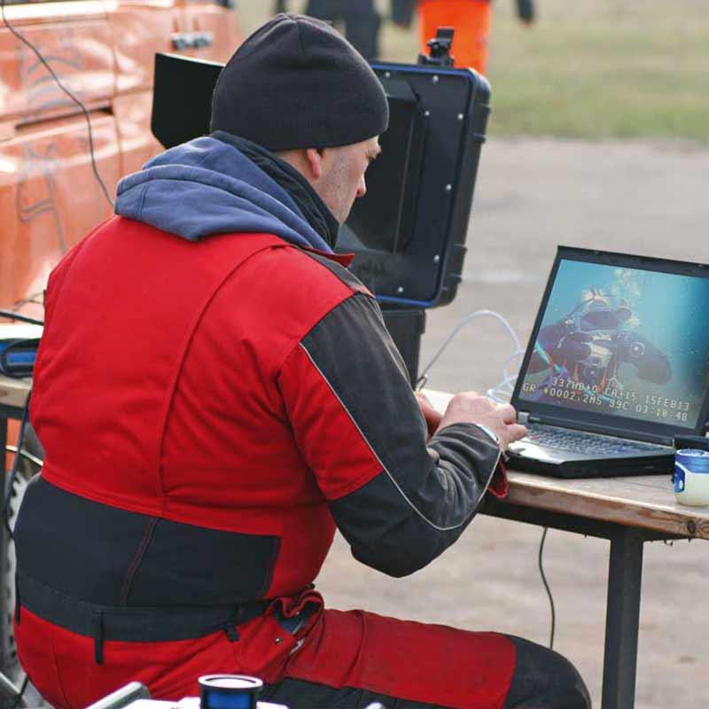 Zwei Berufstaucher kommunizieren via Tauchroboter (ROV) bei einer Anlageninspektion