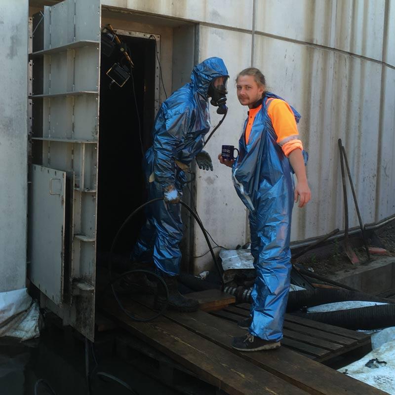 Zwei Industrietaucher in Atemschutzanzügen vor einem Faulturm