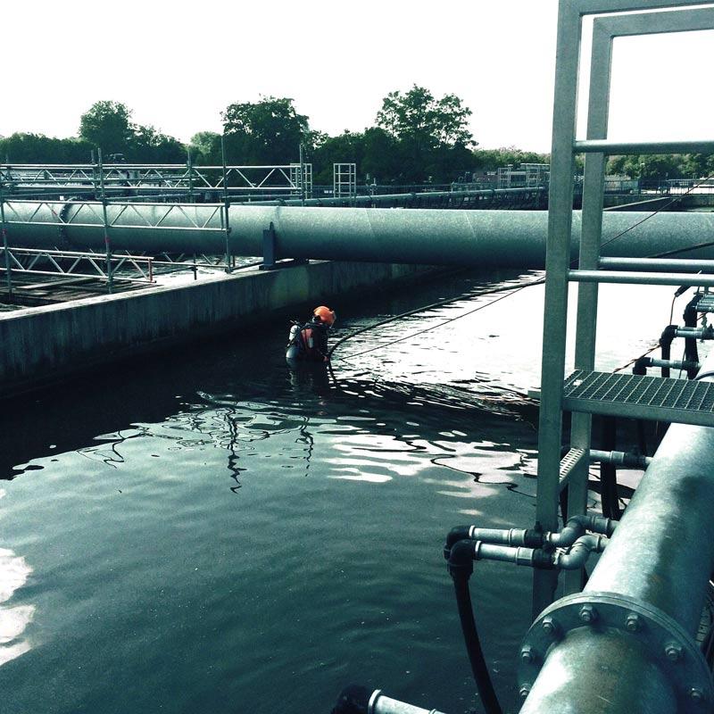 Ein Industrietaucher steht in voller Ausrüstung, knietief im Wasser begutachtet das Wasserbecken einer Industrieanlage
